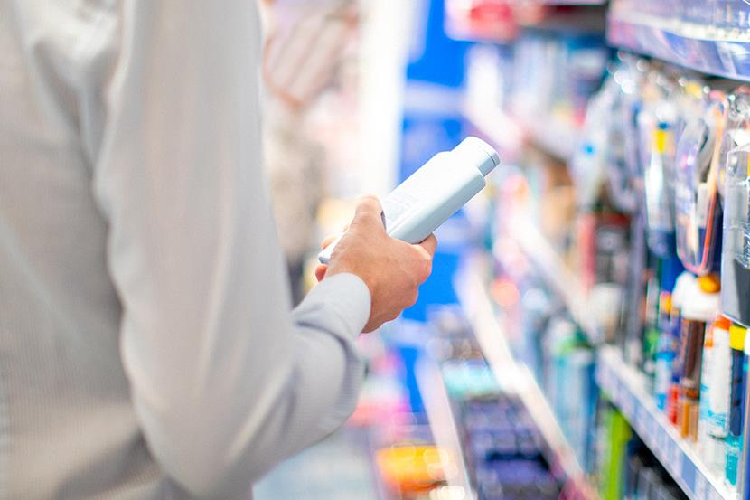 man holding product bottle standing in store aisle