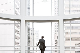 businessman standing looking out large white window of building lobby