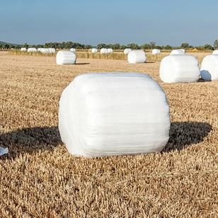 hay bales covered in white plastic wrap sitting in a field