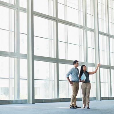 man and woman standing in front of large wall of floor to ceiling windows talking