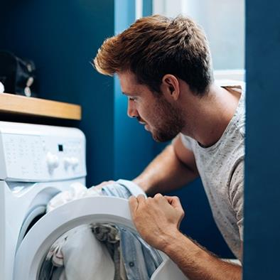 man putting laundry into dryer