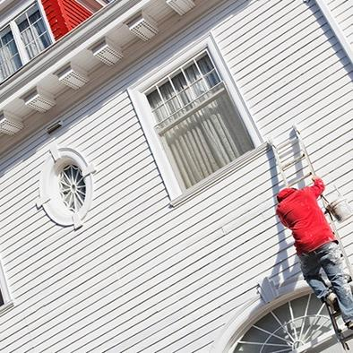 person climbing a ladder against a home exterior with paint can