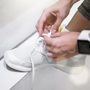 person wearing smartwatch tying laces of white sneaker
