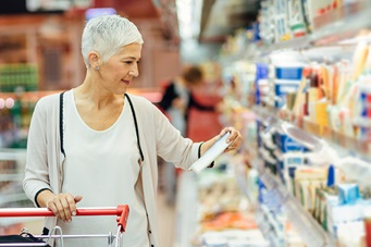 plder smiling woman shopping for groceries in the dairy aisle