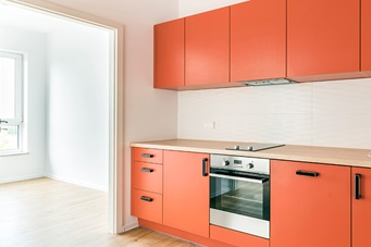 sleek modern kitchen with orange cabinets and cupboards